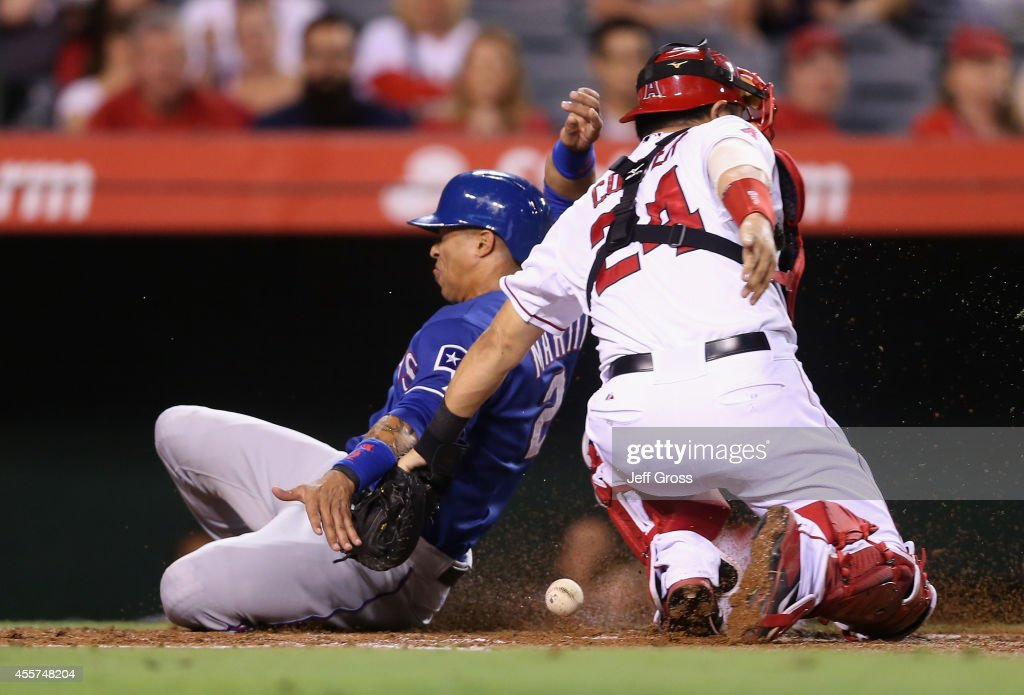 Leonys Martin #2 of the Texas Rangers slides past the tag of catcher <a gi-track='captionPersonalityLinkClicked' href=/galleries/search?phrase=Hank+Conger&family=editorial&specificpeople=713039 ng-click='$event.stopPropagation()'>Hank Conger</a> #24 of the Los Angeles Angels of Anaheim and scores a run on a sacrifice fly by Elvis Andrus in the second inning at Angel Stadium of Anaheim on September 19, 2014 in Anaheim, California.