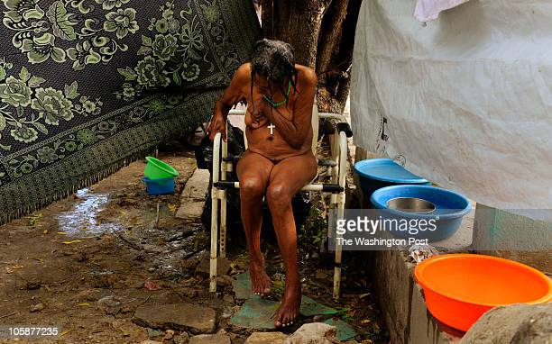 Leronie Belvue a resident at Azil Communal home for the aging population in PortAuPrince Haiti huddles in the chair as she waits to be dressed on...