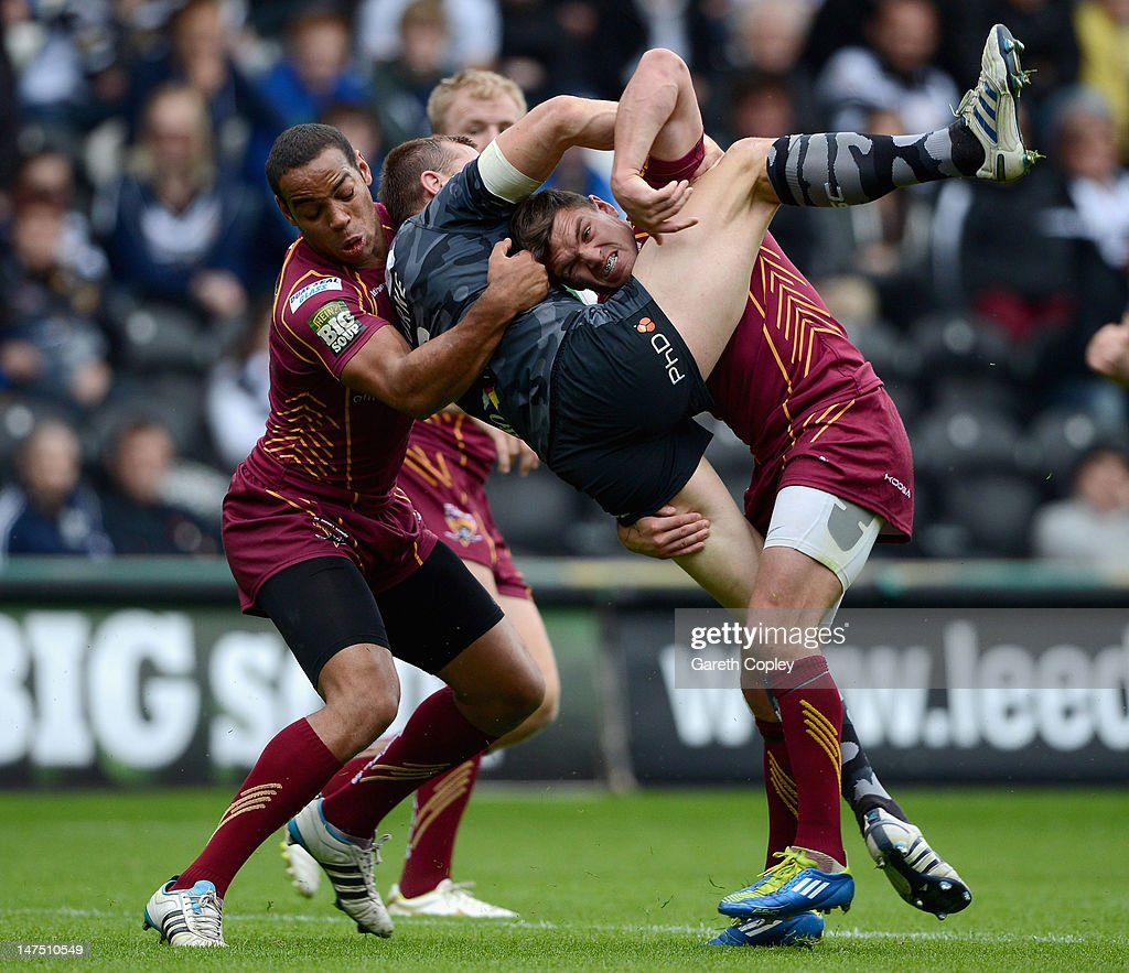 Leroy Cudjoe and Danny Brough of Huddersfield bring Richard Horne of Hull to ground during the Stobart Super League match between Hull FC and...