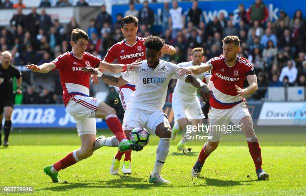 Leroy Fer of Swansea City shoots while under pressure from Marten de Roon of Middlesbrough and Ben Gibson of Middlesbrough during the Premier League...