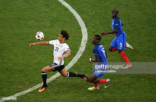 Leroy Sane of Germany controls the ball under pressure from Paul Pogba and N'Golo Kante of France during the UEFA EURO semi final match between...