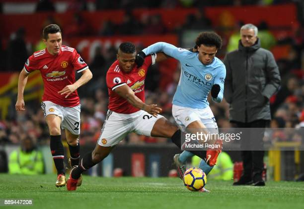Leroy Sane of Manchester City and Antonio Valencia of Manchester United clash as Jose Mourinho Manager of Manchester United and Ander Herrera look on...