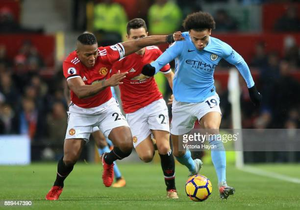 Leroy Sane of Manchester City and Antonio Valencia of Manchester United clash as Ander Herrera looks on during the Premier League match between...