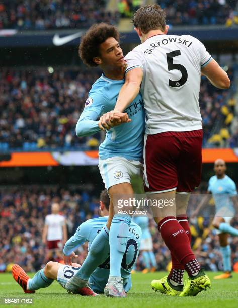 Leroy Sane of Manchester City and James Tarkowski of Burnley clash as Bernardo Silva of Manchester City is fouled for a penalty during the Premier...