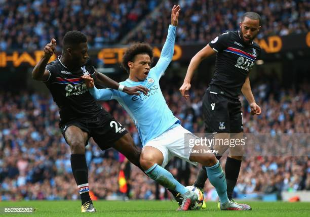 Leroy Sane of Manchester City is chellenged by Timothy FosuMensah and Andros Townsend of Crystal Palace during the Premier League match between...