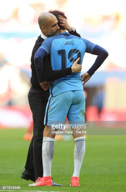 Leroy Sane of Manchester City is consoled by manager Josep Guardiola after the Emirates FA Cup SemiFinal match between Arsenal and Manchester City at...