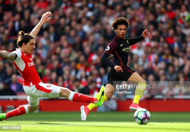 Leroy Sane of Manchester City scores his sides first goal as Hector Bellerin of Arsenal attempts to block during the Premier League match between...