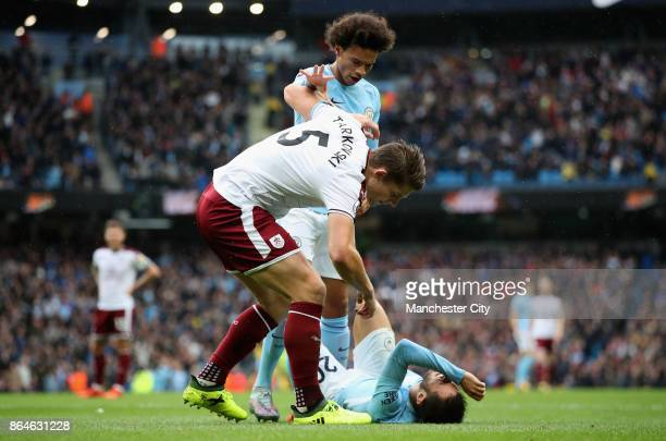 Leroy Sane of Manchester City speaks with James Tarkowski of Burnley after Bernardo Silva of Manchester City falls down during the Premier League...