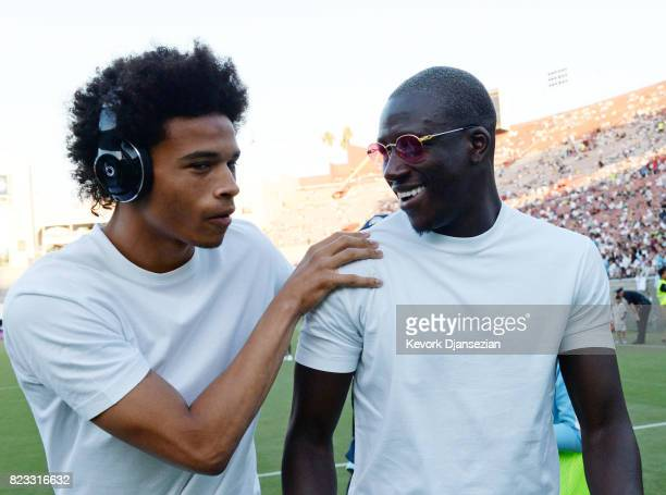 Leroy Sane of Manchester City talks with new defender Benjamin Mendy during warm ups before the start of soccer match Real Madrid during the...