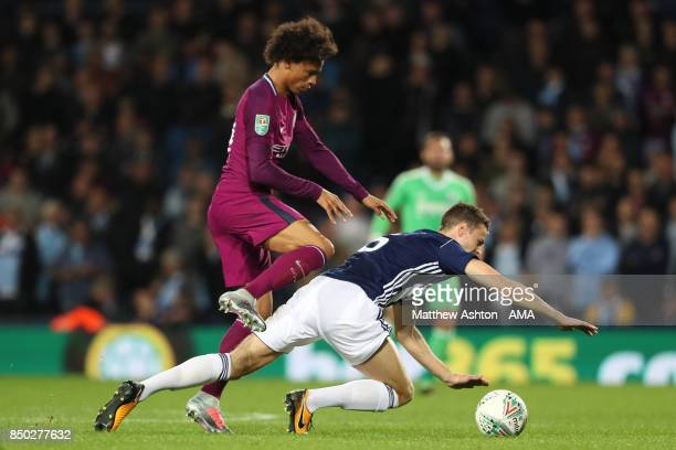 Leroy Sane of Manchester City tangles with Jonny Evans of West Bromwich Albion during the Carabao Cup third round match between West Bromwich Albion...