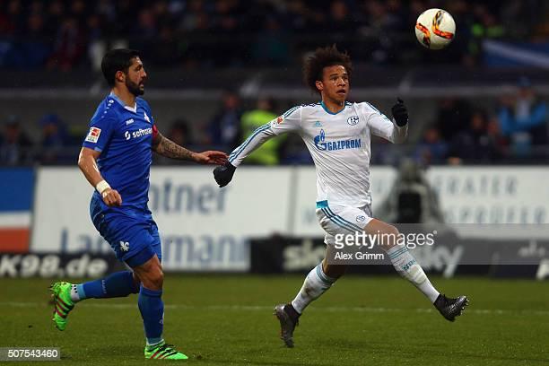 Leroy Sane of Schalke is challenged by Aytac Sulu of Darmstadt during the Bundesliga match between SV Darmstadt 98 and FC Schalke 04 at MerckStadion...