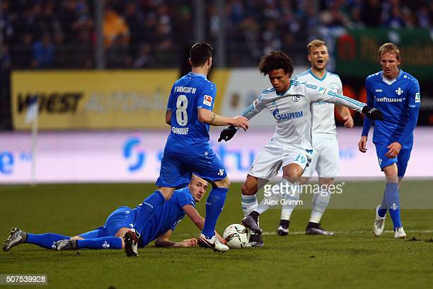 Leroy Sane of Schalke is challenged by Jerome Gondorf Luca Caldirola and Jan Rosenthal of Darmstadt during the Bundesliga match between SV Darmstadt...