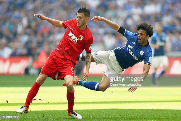 Leroy Sane of Schalke is tackled and stopped by Jeffrey Gouweleeuw of FC Augsburg during the Bundesliga match between FC Schalke 04 and FC Augsburg...