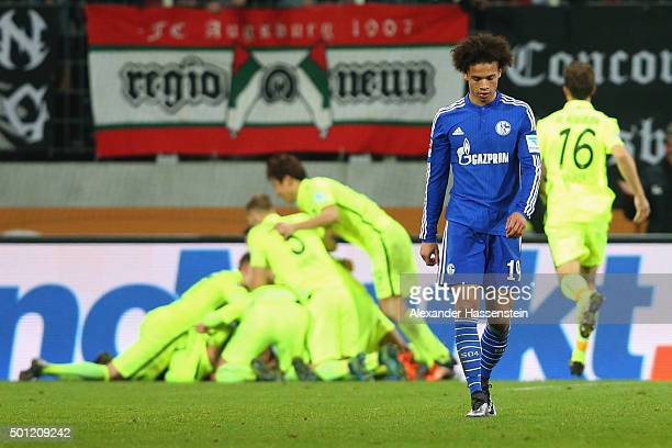 Leroy Sane of Schalke looks dejected whilst players of Augsburg celebrate the winning goal during the Bundesliga match between FC Augsburg and FC...