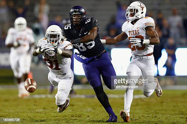 Leroy Scott of the Texas Longhorns breaks up and pass intended for LaDarius Brown of the TCU Horned Frogs as Carrington Byndom of the Texas Longhorns...