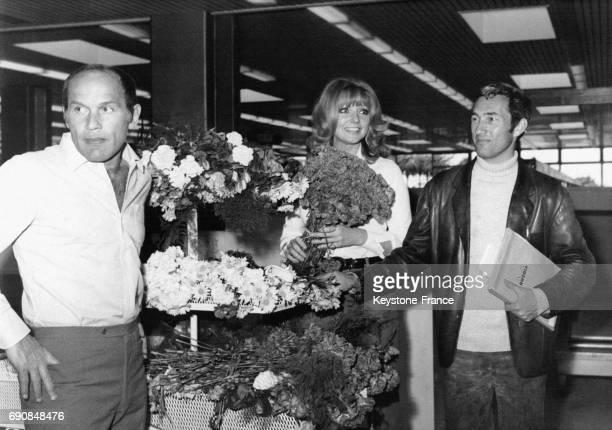Les acteurs Marcel Bozzuffi et Sylva Koscina et le réalisateur JeanPierre Desagnat sur un stand de fleurs en tournage à l'aéroport de Nice en France