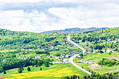 Les Eboulements, Charlevoix, Quebec, Canada cityscape or skyline with main highway steep curvy road going vertically up, patch farm green dandelion field, scattered village houses