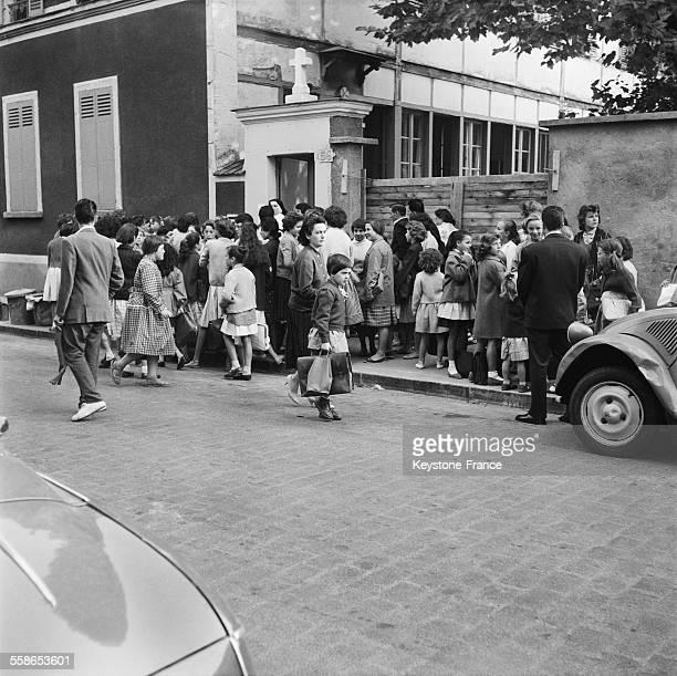 Les fillettes avec leurs blouses et cartables accompagnées de leurs parents sont accueillies par une sœur à la porte de l'établissement scolaire...