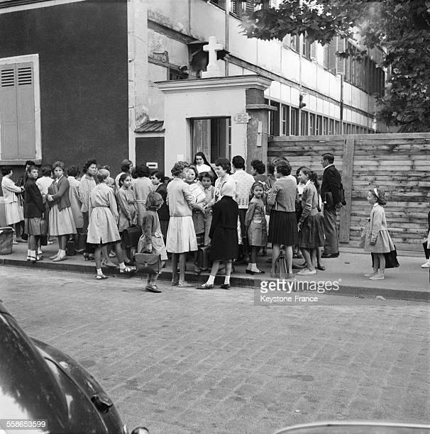 Les fillettes avec leurs blouses et cartables sont accueillies par une sœur à la porte de l'établissement scolaire SteMariedelaProvidence à...