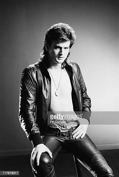 Les McKeown British pop singer poses barechested beneath a black leather jacket with a medallion hanging from a chain around his neck in a studio...