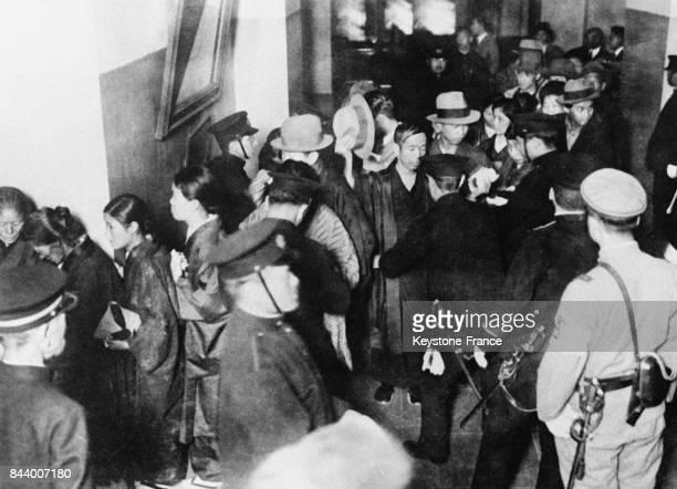 Les personnes assistant au procès de communistes sont fouillées par la sécurité à leur arrivée au tribunal le 1er décembre 1932 à Tokyo Japon