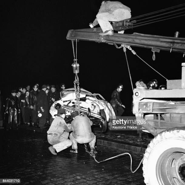 Les pompiers relèvent la voiture tombée du haut du pont du chemin de fer à l'aide d'un camiongrue à Paris France le 29 février 1956