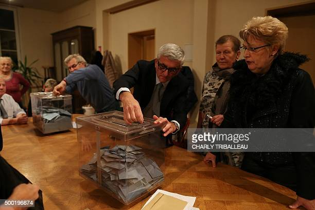 Les Republicains rightwing party top candidate for the regional elections in Normandie Herve Morin unlocks a ballot box prior to take part in the...