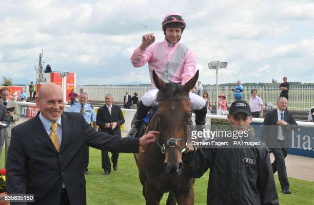 Les Reynolds representing Trainer John Gosden leads Dar Re Mi and jockey Jimmy Fortune after winning the Audi Pretty Polly Stakes during the Audi...