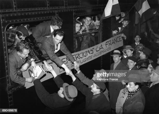 Les réfugiés allemands disent au revoir à leurs amis au départ du train à la Gare de Lyon pour se rendre en Palestine on remarque une banderole sur...