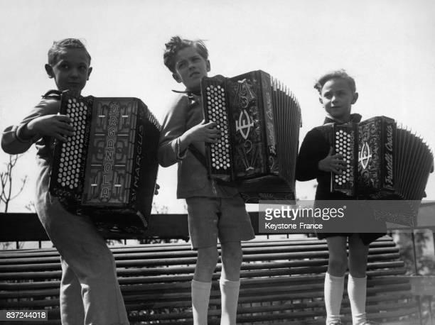 Les trois plus jeunes candidats du concours Jules Nicoli 7 ans Marcel Roban 9 ans et Jean Gardon 6 ans jouent debout sur un banc de Montmartre le 5...