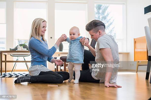 Lesbian couple assisting baby to walk at home