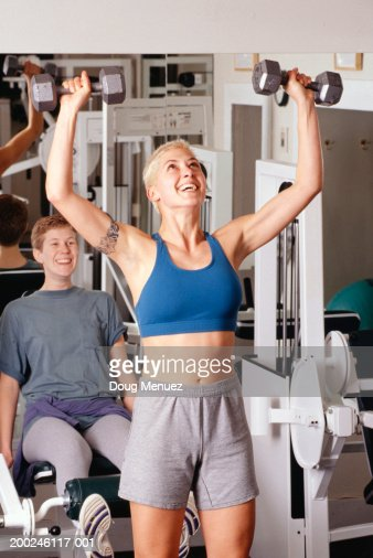 Lesbian Couple At Gym One Working Out With Dumbbells Stock Photo ...