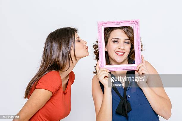Lesbian couple fooling around with pink picture frame smiling, puckering lips