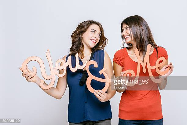 Lesbian couple holding the words you and me face to face smiling