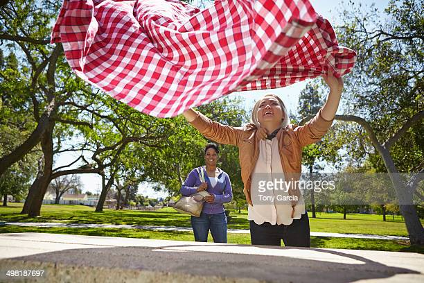 Lesbian couple preparing table cloth for picnic bench in park