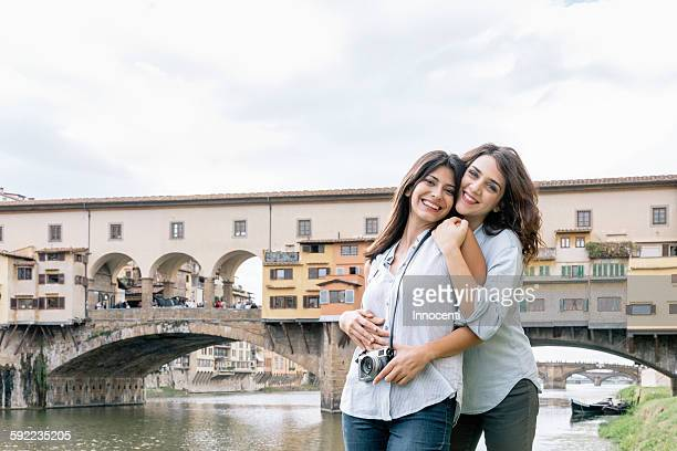 Lesbian couple standing hugging in front of Ponte Vecchio and river Arno looking at camera smiling, Florence, Tuscany, Italy
