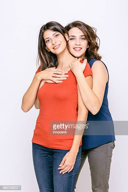 Lesbian couple standing hugging looking at camera smiling