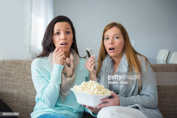 lesbian couple watching movie together, surpised