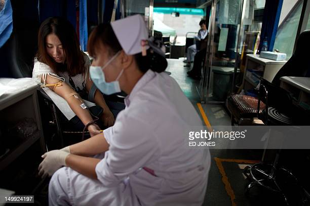 Lesbian Meng Ru gives blood as a nurse waits at a blood donation bus in Beijing on August 7 2012 For the first time in 14 years lesbians in China are...