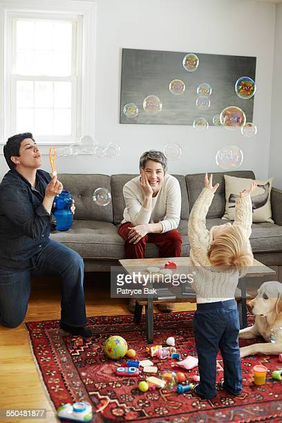 Lesbian moms & daughter play in the living room