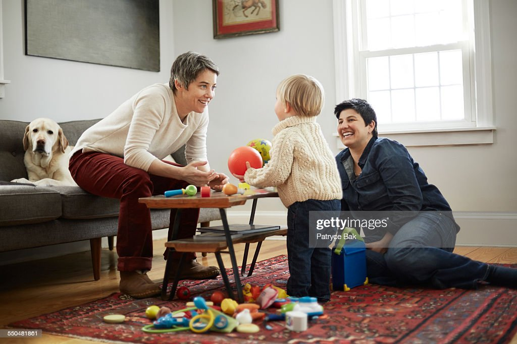 Lesbian moms play w/ their daughter in living room : Stock Photo
