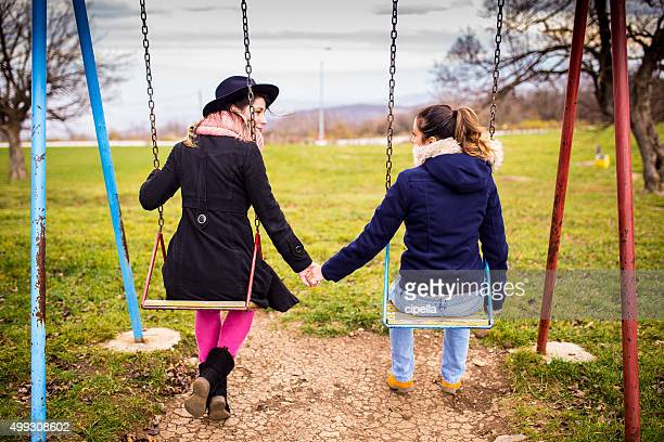 Lesbians on swing,holding hands