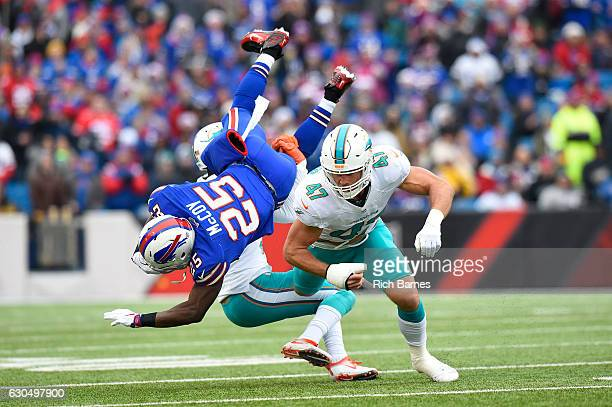 LeSean McCoy of the Buffalo Bills is upended by Michael Thomas of the Miami Dolphins and Kiko Alonso of the Miami Dolphins during the first half at...