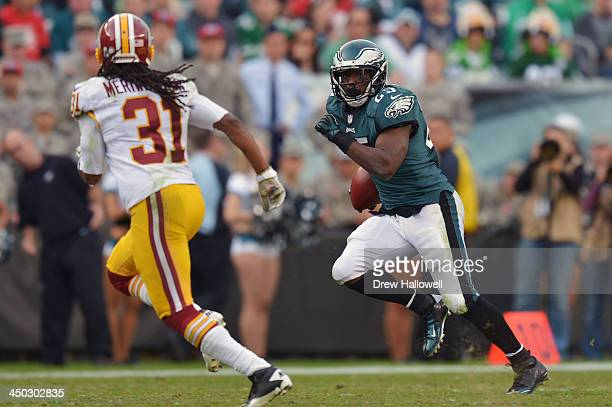 LeSean McCoy of the Philadelphia Eagles runs past Brandon Meriweather of the Washington Redskins at Lincoln Financial Field on November 17 2013 in...