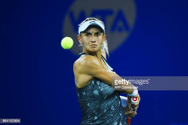 Lesia Tsurenko of Ukraine hits a return against Garbine Muguruza of Spain during their second round women's singles match at the WTA Wuhan Open...