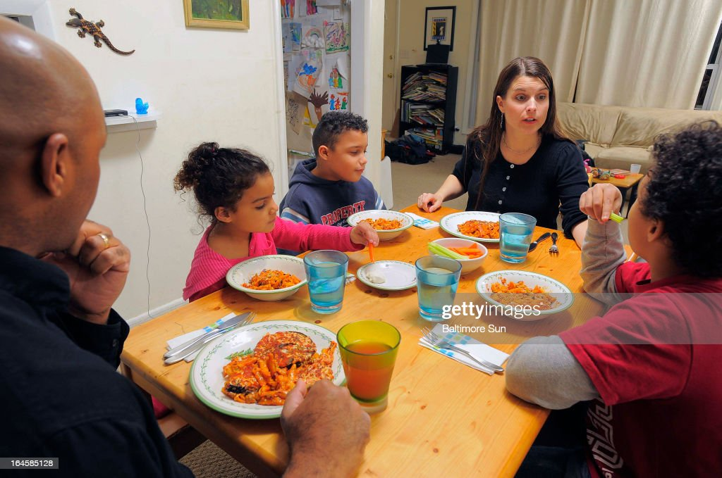 Lesley and Ray Parker-Rollins (at ends of table) and their children Will, 10 (blue sweatshirt), Maya, 5 and Tyler, 11 eat dinner together at their Lutherville-Timonium, Maryland home, March 7, 2013.