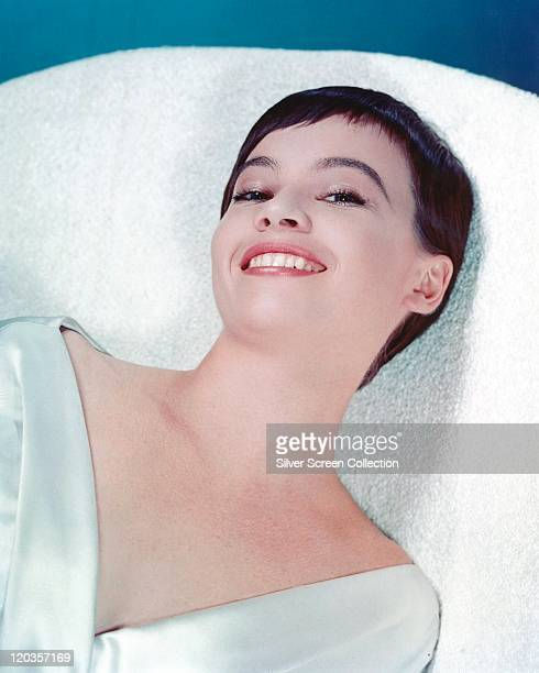 Leslie Caron French actress smiling while reclining on a white towelling surface circa 1955