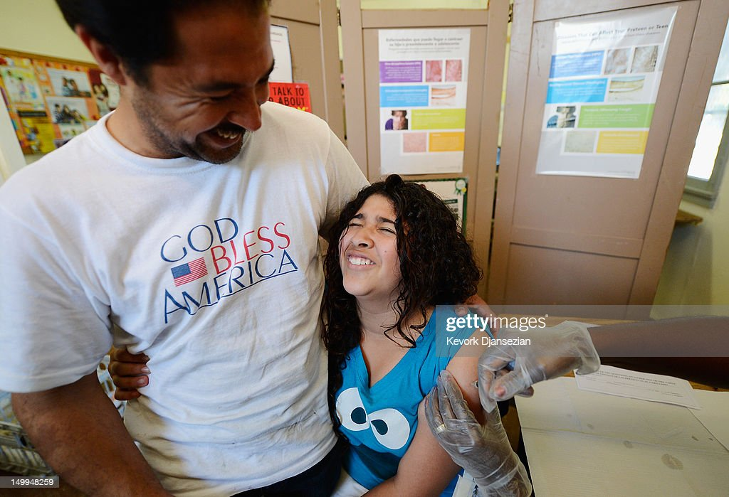 Leslie Cervantes, 11, from Palms Middle School, holds on to her father Hector Cervantes as she receives a vaccine against whooping cough at Mark Twain Middle School August 7, 2012 in Los Angeles, California. The boosters, also called Tdap shots, are required of all seventh graders before they can start school. The Los Angeles Unified School District is offering free shots at various clinics in the city to help students make the deadline before school start on August 14.