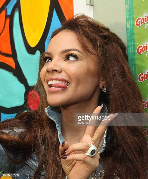 Leslie Grace takes a selfie with her phone at the 'Portraits Of Hope' Community Unveiling event by Gain at Happy Family Laundromat in The Bronx on...