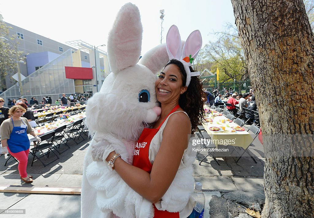 Leslie Hughes with the reality television show 'The Bachelor' gets a hug from the Easter bunny as she volunteers to serve dinner during the Skid Row Easter event at the Los Angeles Mission on March 29, 2013 in Los Angeles, California. Volunteers, celebrities and nurses distributed more than 1000 Easter baskets to children and provided 3,500 hot meals, 2,000 pairs of shoes and and podiatric care to the homeless of Skid Row.